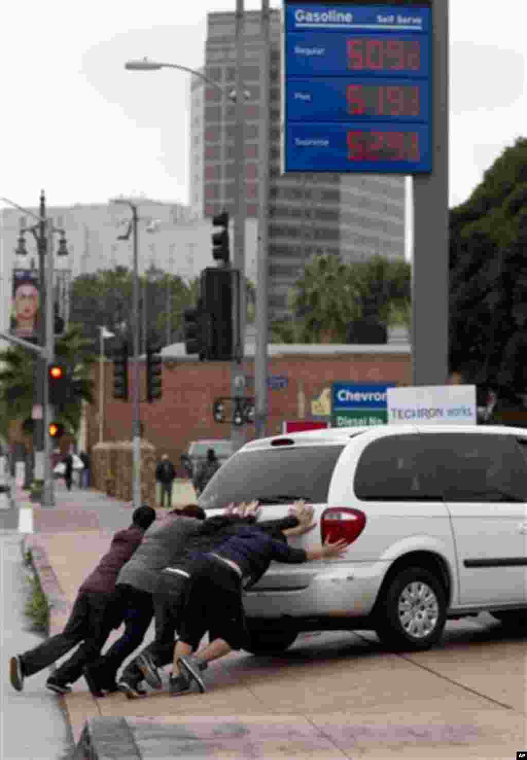 Pedrestrians help push a motorist who ran of gas into a station downtown Los Angeles on Friday, March 16, 2012. Higher gas prices could force consumers to cut back on discretionary spending and could weigh on growth and slow hiring in the nation.(AP Photo
