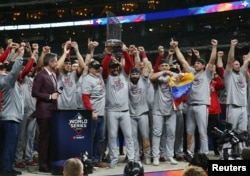 Washington Nationals manager Dave Martinez and his team hoist the Commissioners Trophy after defeating the Houston Astros in game seven of the 2019 World Series in Houston, Texas, October 30, 2019.