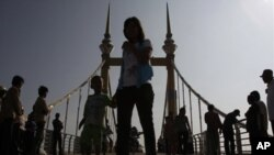 Cambodians walk on a bridge (now removed) on which hundreds of people stampeded during a water festival on Nov. 22, 2010.