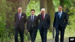 Foreign Ministers of France Laurent Fabius, Ukraine Pavlo Klimkin, Germany Frank-Walter Steinmeier and Russia Sergey Lavrov, from left, go for a walk before a meeting at the Guesthouse of Foreign Ministry Villa Borsig in Berlin, Sunday, Aug. 17, 2014.