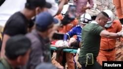 柬埔寨救援人员2019年6月22日从西哈努克市一处正在建造中的7层倒塌建筑中救助一名幸存者。