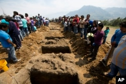 Mourners gather around open graves as they prepare to bury 11 young people between the ages of 4 and 18 killed in a fireworks explosion, in the village of San Isidro, Puebla state, Mexico, May 10, 2017.