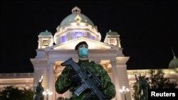 Ilustrasi: Seorang prajurit tentara Serbia berjaga di depan gedung parlemen saat jam malam diberlakukan untuk mencegah penyebaran korona di Beograd, Serbia, 18 Maret 2020. (Foto: Reuters /Marko Djurica)
