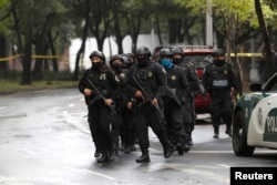 Police officers arrive at the area where a shooting took place in Mexico City, Mexico, June 26, 2020.