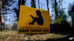 """A sign that reads """"our children deserve better safe choice now"""" is seen on Friday, Jan. 15, 2021, in Decatur, Ga., just down the road from the U.S. Centers for Disease Control and Prevention. (AP Photo/Brynn Anderson)"""