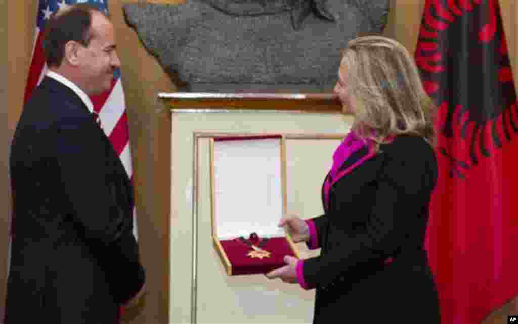 Albanian President Bujar Nishani presents US Secretary of State Hillary Clinton with the Order of the National Flag following meetings at the Palace of the Brigades in Tirana, Albania, Thursday, Nov. 1, 2012. Hillary Clinton arrived in EU-hopeful Albania