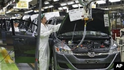 Workers give a final check on the Honda Accord Tourer at Honda Motor Co.'s Saitama Factory in Sayama, north of Tokyo, April 18, 2011