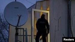 Seorang polisi Jerman berdiri di depan pintu kaca yang pecah di Masjid Bilal, Frankfurt, negara bagian Hesse, 1 Februari 2017. (Foto: dok).