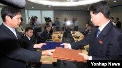 14일 개성공단 종합지원센터에서 열린 제7차 개성공단 남북당국실무회담이 타결된 후, 남북한 대표단이 합의서를 교환하고 있다.