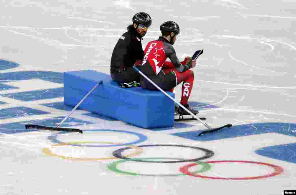 Canadian short track speed skaters and brothers Charles and Francois Hamelin watch a replay of their training on an iPad at the Iceberg Skating Palace, Feb. 4, 2014.