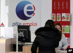 FILE - A job seeker speaks to a clerk at an Employment Center in Marseille, southern France, Feb. 24, 2015. Record-high unemployment started dragging French President Francois Hollande's popularity down just a few months after his election in 2012.