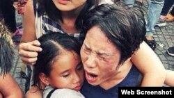 Bà Hoàng Mỹ Uyên ôm con gái trong vụ xô xát giữa lực lượng an ninh Việt Nam với người biểu tình hôm 8/5 ở Sài Gòn.
