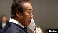 Представник організаційного комітету Олімпіади в Токіо одягає маску на засіданні ради 30 березня 2020 р.