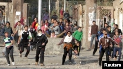 FILE - Students of Al-Azhar University, who are supporters of the Muslim Brotherhood and deposed Egyptian President Mohammed Morsi, clash with riot police and residents at the university campus in Cairo's Nasr City district on January 8, 2014.