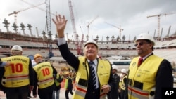 ប្រធាន FIFA លោក Sepp Blatter (រូបឆ្វេង) បក់ដៃដាក់មនុស្សម្នាក្នុងពេលធ្វើទស្សនៈកិច្ចទៅកាន់ស្តាតមួយក្នុងចំណោមស្តាតទាំងអស់សម្រាប់ធ្វើការប្រកួត World Cup ក្នុងឆ្នាំ២០១០ ដែលស្តាតនោះមានទីតាំងនៅក្រុង Cape Town កាលពីថ្ងៃច័ន្ទ ទី១៥ ខែកញ្ញា ឆ្នាំ២០០៨។