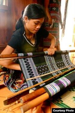 Một người phụ nữ A Lưới đang dệt một tấm vải thổ cẩm