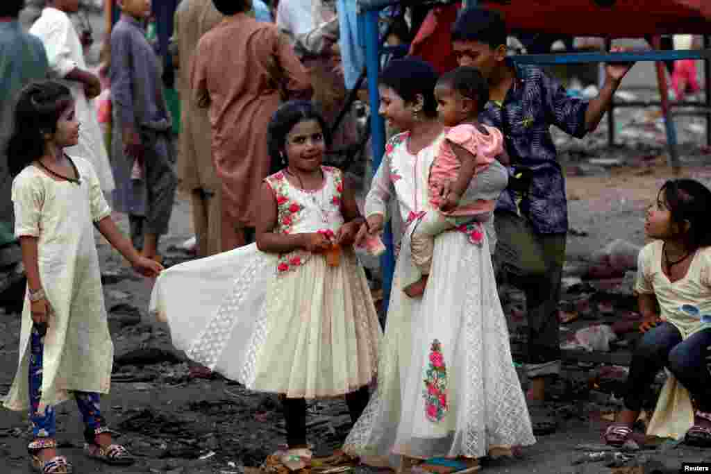Siblings in new dresses stand beside a swing at a playground in a poor neighborhood on the last day of Eid al-Adha celebrations in Karachi, Pakistan.