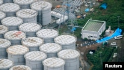 FILE - An aerial view of workers wearing protective suits and masks working atop contaminated water storage tanks at the Fukushima Daiichi nuclear power plant.