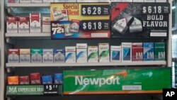 FILE - Packs of cigarettes are offered for sale at a convenience store in Helena, Montana, May 18, 2017. Tobacco companies were ordered to include new statements on cigarette packages by November 2018.
