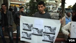 A protester in Ramallah holds a picture of a young Gazan girl and says the violence must stop. He blames Israel but says his leadership must do more. (R.Collard/VOA)