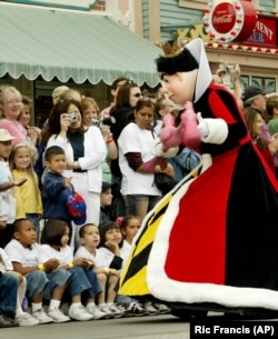 "An actor dressed as the ""Queen of Hearts"" from ""Alice in Wonderland"" entertains children during ""Walt Disney's Parade of Dreams"" at Disneyland in California, 2005. (AP/Ric Francis)"