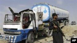 پاسهوانێـکی هێزهکانی ئاسایشی پاکستان له پاڵ تانکهرێـکی سووتهمهنیدا وهستاوه که هێرشی کراوهته سهر، پـێـنجشهممه 30 ی نۆی 2010
