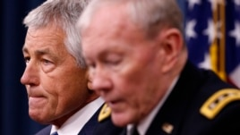 U.S. Defense Secretary Chuck Hagel (L) listens as Chairman of the Joint Chief of Staff General Martin Dempsey (R) speaks during a briefing on the Defense Department's FY2014 budget at the Pentagon, Apr. 10, 2013.