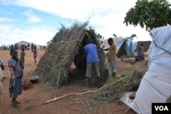 Refugees erecting new shelters at Kapise II camp. (Lameck Masina/VOA)
