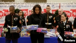 "Ibu Negara AS Michelle Obama (tengah) saat menyortir hadiah untuk anak-anak bersama Korps Marinir AS Sersan David Hayes (kiri) dan Sersan Catalina Perez (kanan) di Kampanye Program Korps Marinir AS ""Toys For Tots"" di Joint Base Anacostia-Bolling, Washington (19/12)."