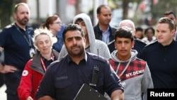 برطانوی بارڈر فورس کے اہل کار سرپرست کے بغیر برطانیہ پہنچنے والے پچوں کے ایک گروپ کو امیگریشن جج کے پاس لے جارہے ہیں۔ اکتوبر 2016