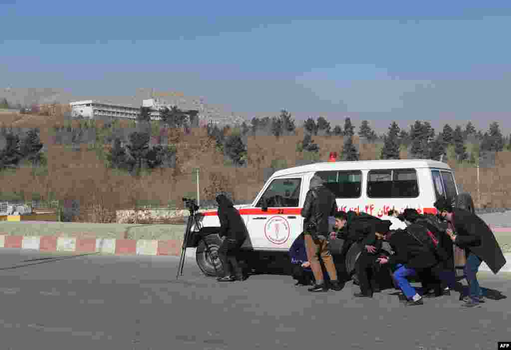Afghan journalists take cover behind an ambulance near the Intercontinental Hotel during a fight between gunmen and security forces in Kabul. Gunmen stormed the luxury hotel, killing at least six people, including a foreigner, sparking a twelve hour fight with security forces that left terrified guests scrambling to escape and parts of the building ablaze.