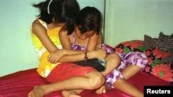 Hai bé gái người Việt 8 tuổi và 10 tuổi ngồi trên một chiếc giường trong một nhà thổ ở tại làng Svay Pak, gần Phnom Penh, Campuchia. (Ảnh tư liệu).
