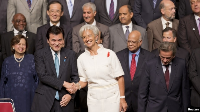 International Monetary Fund (IMF) Managing Director Christine Lagarde shakes hands with Japanese Finance Minister Koriki Jojima before posing for a group photograph in Tokyo, October 12, 2012.