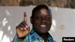 FILE - Current President Jose Mario Vaz shows his inked finger after voting in Bissau, Guinea-Bissau, April 13, 2014.
