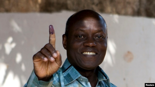 FILE - PAIGC party's candidate Jose Mario Vaz shows his inked finger after voting in Bissau, Guinea-Bissau, April 13, 2014.