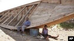Des survivants assis près d'une pirogue similaire à une autre qui a fait naufrage, à Goma, RDC, 5 septembre 2006.