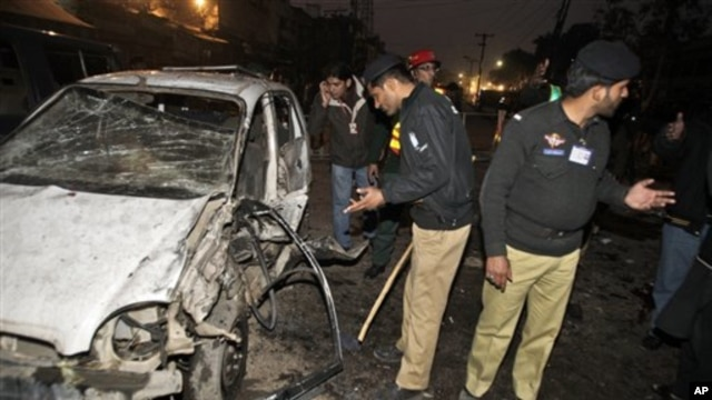 Pakistani police officers check the site of a suicide bombing in Lahore, Pakistan, 25 Jan 2011