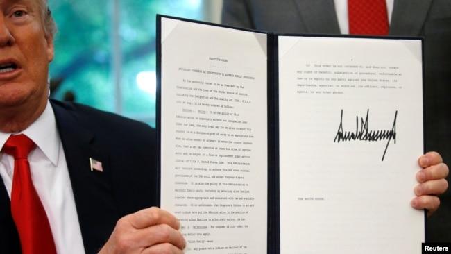 El presidente Donald Trump muestra una orden ejecutiva sobre la política de inmigración después de firmarla en la Oficina Oval en la Casa Blanca en Washington, junio 20, 2018.