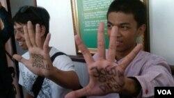 """Muhammad Arif (kanan), menunjukkan telapak tangannya yang bertuliskan """"Jogja Ora Didol (Jogja Tidak Dijual)"""", sebelum disidang di PN Yogyakarta, Kamis (10/10). (VOA/Nurhadi Sucahyo)"""