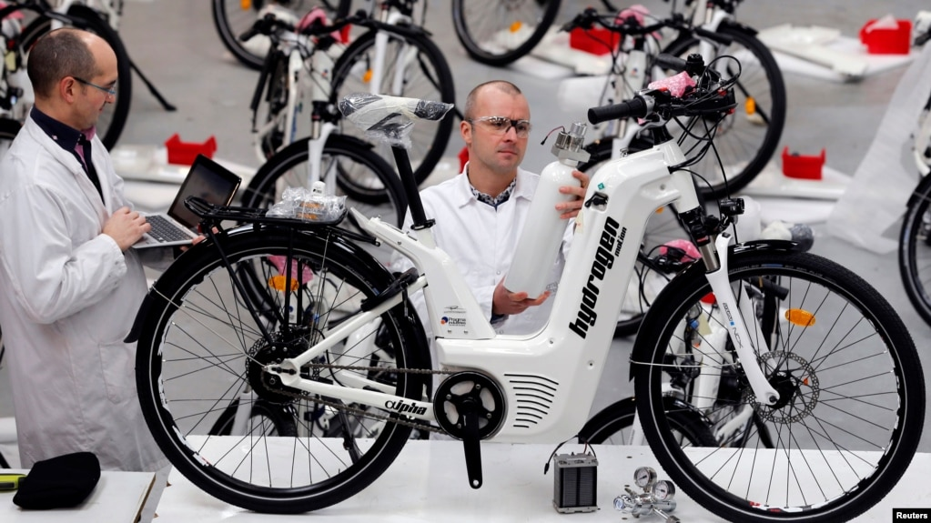 Pierre Forte (R), founder and CEO of Pragma Industries, and Alexandre Blanc (L), operations director, check an Alpha bike, first industrialized bicycle to use a hydrogen fuel cell at the Pragma Industries factory in Biarritz, France, Jan. 15, 2018.