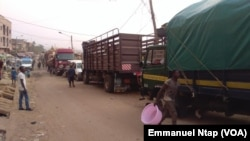 Des camions stationnés au Marché 8e attendent les chargements des filets d'oignons pour le Gabon, à Yaoundé, Cameroun, 20 février 2017. (VOA/Emmanuel Ntap).