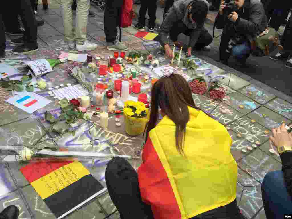Woman draped in Belgian flag places memento at makeshift memorial in honor of terror bombing victims in Brussels, Belgium, March 23, 2016. (N. Pourebrahim / VOA )