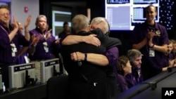 ຜູ້ກຳກັບໂຄງການ Cassini ທ່ານ Earl Maize (ກາງ) ແລະ ຜູ້ອຳນວຍການ ຄວບຄຸມການບິນ ກອດກັນ ທີ່ຫ້ອງຄວບຄຸມ ຂອງອົງການອະວະກາດ NASA. (ວັນທີ 15 ກັນຍາ 2017)