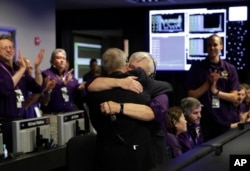 Project manager Earl Maize, center left, and flight director Julie Webster hug in mission control at NASA's Jet Propulsion Laboratory, Sept. 15, 2017, in Pasadena, Calif., after confirmation of Cassini's demise.