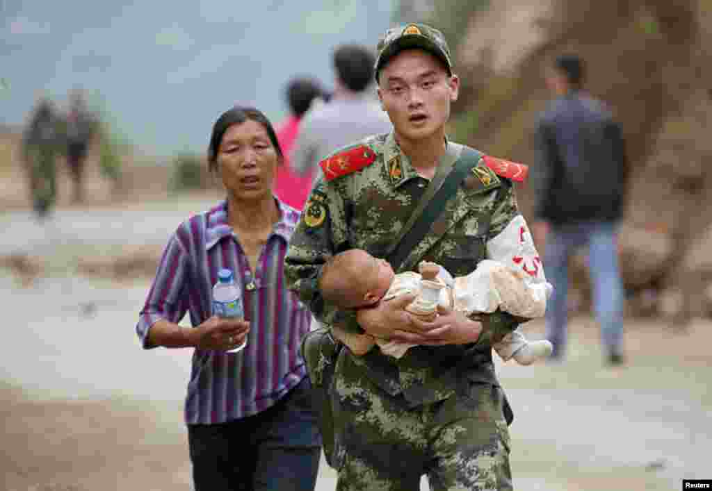 A paramilitary policeman carries a baby in his arms after an earthquake hit Ludian county of Zhaotong, Yunnan province, China, Aug. 3, 2014.