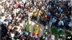 Anti-government protesters carry coffins of Sunni Muslim villagers killed in Hula, near Homs, Nov. 2, 2011.