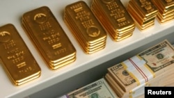 FILE - Gold bars and U.S. dollar bills.