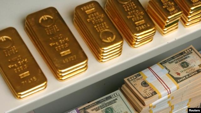 FILE - Gold bars and U.S. dollar bills.