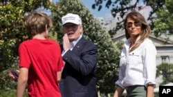 President Donald Trump, center, with first lady Melania Trump and their son Barron Trump, responds to a reporter's question upon arrival at the White House in Washington, from Camp David in Maryland, June 18, 2017.