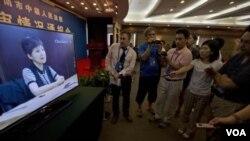 ບັນດານັກຂ່າວ ພາກັນເບິ່ງຄຳໃຫ້ການ ຂອງ ນາງ Gu Kailai ພັນລະຍາ ທ່ານ Bo Xilai.
